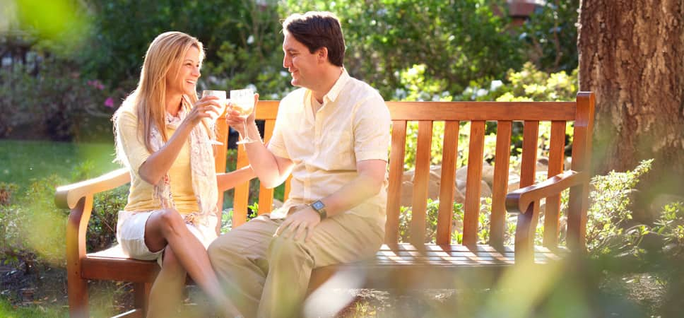 A couple sits on a bench and, in the warm glow of the California sun, raise a glass of white wine to each other.