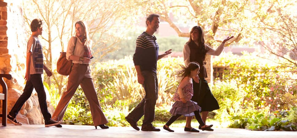 A family of 4 follows a tour guide through the grounds of Disney's Grand Californian Hotel & Spa.