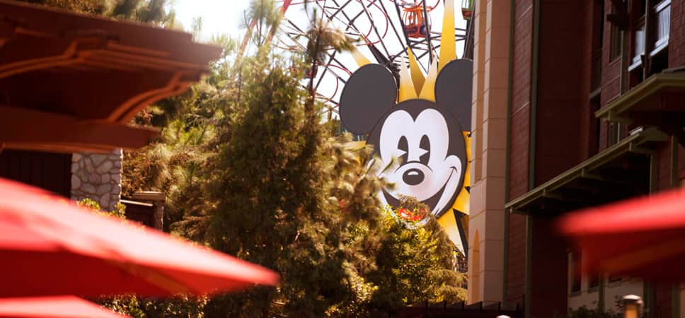 Through the trees, see the iconic face of Mickey Mouse on Mickey's Fun Wheel, a Disney California Adventure Park attraction.