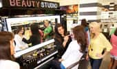 Inside the Beauty Studio shop, women gather to try make-up.