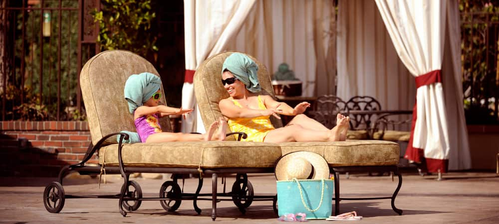 A mother and daughter stretch out on lounge chairs and compare their nails.