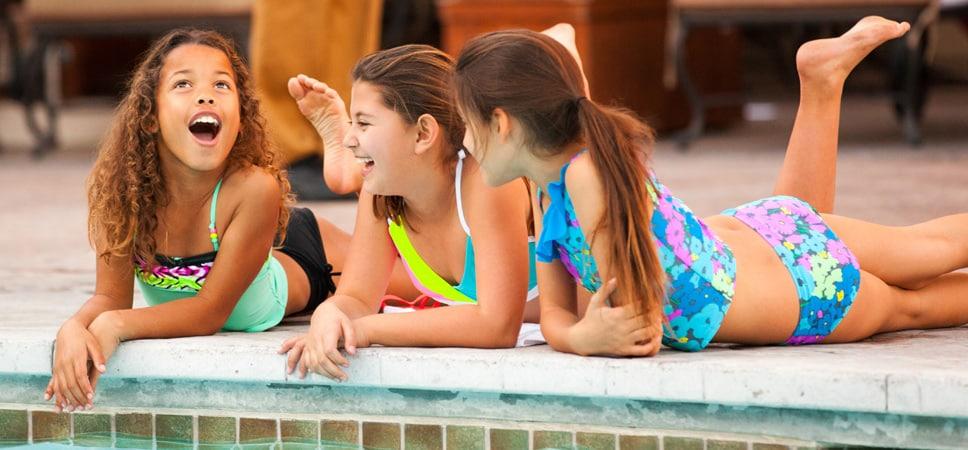 3 niñas se reúnen a la orilla de la piscina y ríen