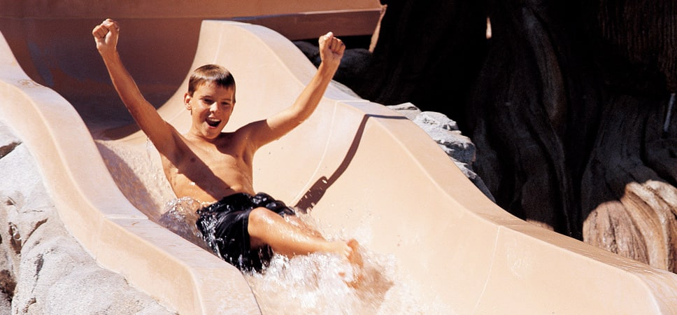 A boy has fun on a water slide at Disney's Grand Californian Hotel & Spa pool.