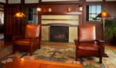 Luxurious leather armchairs flank the fireplace.