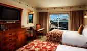 From the 2 queen-size beds see the TV, dresser and exit to balcony with partial theme park view