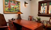 A impressive workstation with luxurious leather chair, impressive wood desk and Arts and Crafts-inspired artwork.
