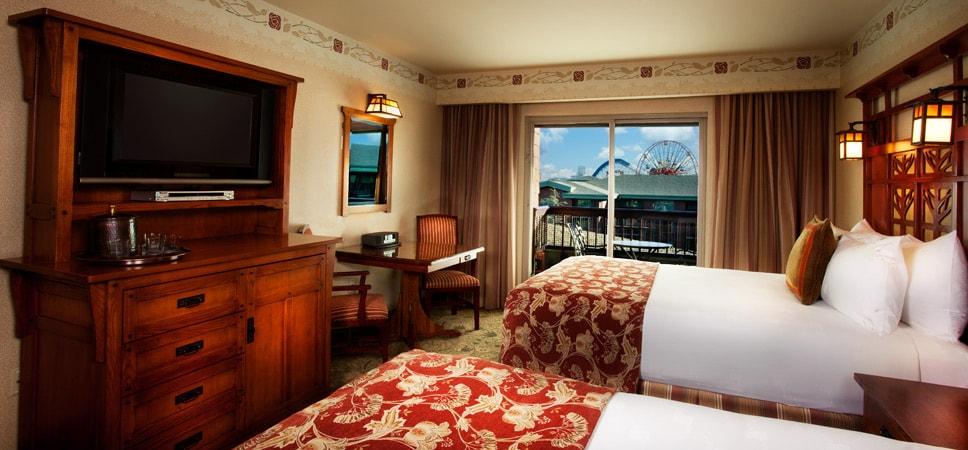 Desde las 2 camas queen puede verse el televisor, el armario y la salida al balcón con vista parcial del Parque.