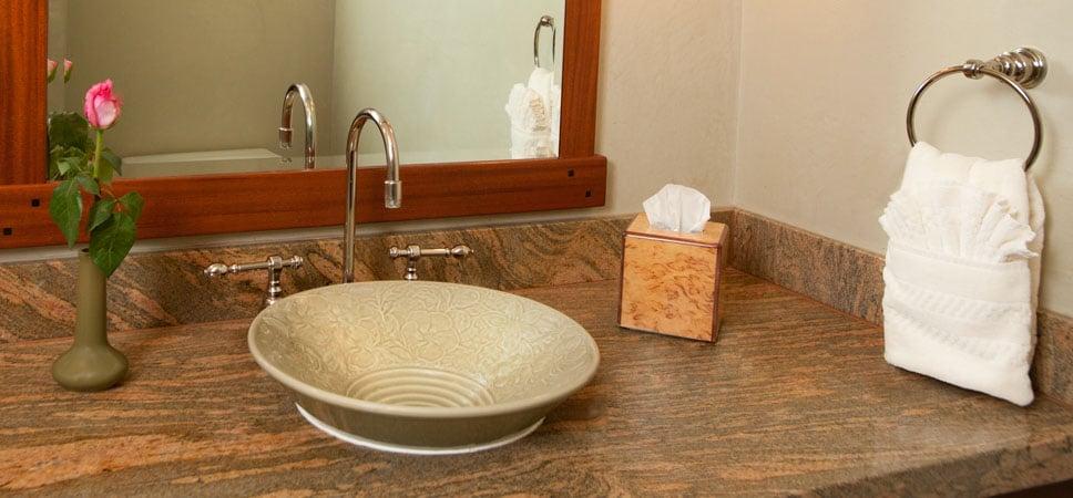 Sencillo lavabo de cerámica en suave tono verde con un sutil y delicado diseño floral