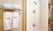 Toma de suaves toallas y una elegante ducha de azulejos blancos
