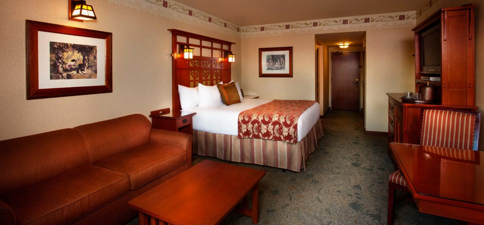 Rich red sofa sits next to a king-size bed in a Standard room with premium view and Club Level services