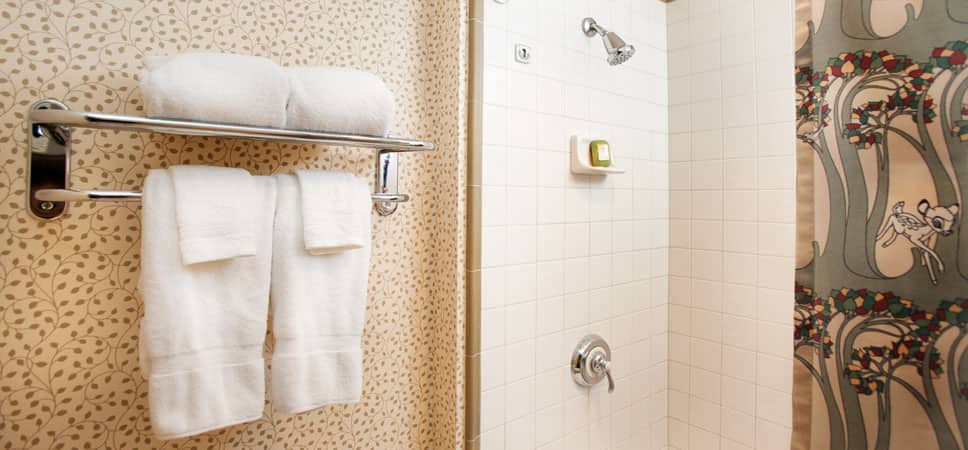 Shot of fluffy towels and an elegantly white-tiled shower
