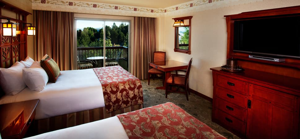 Wide shot of room with 2 queen-size beds and surroundings, like television and glass balcony door