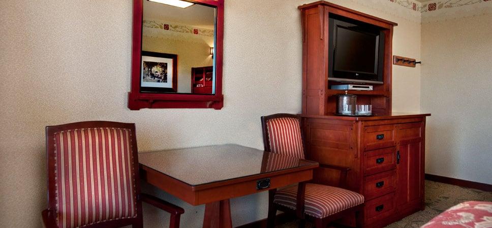 Mesa con 2 sillas, cómoda con cafetera y un espejo que refleja la belleza de la habitación.