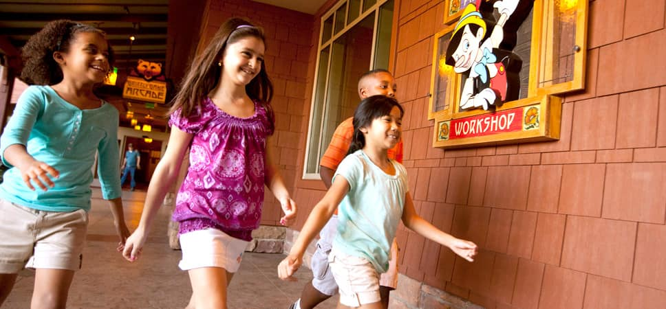 4 young Guests are excited to enter Pinocchio's Workshop.