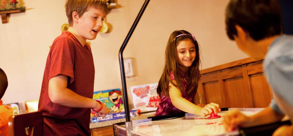 Close up on kids playing air hockey.