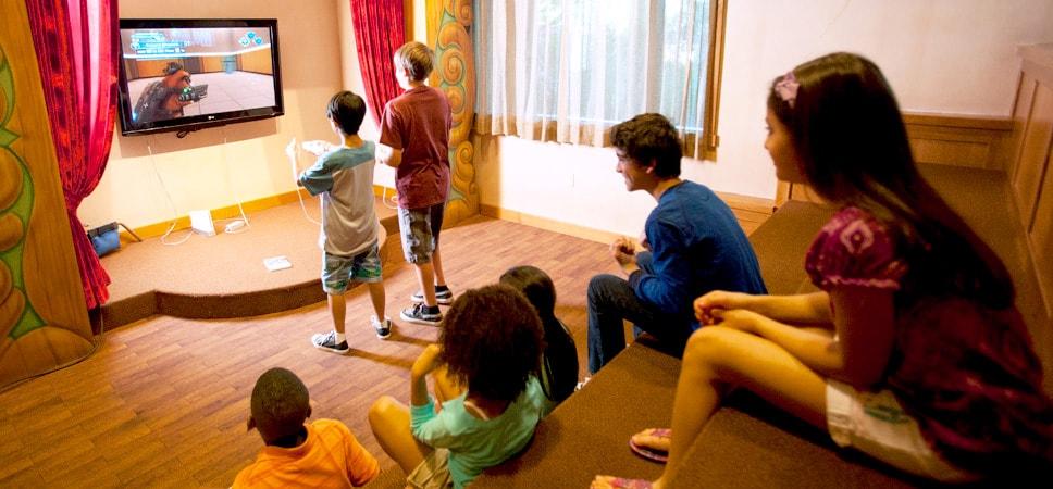 Niños jugando videojuegos mientras otros observan en el área de teatro del taller Pinocchio's Workshop