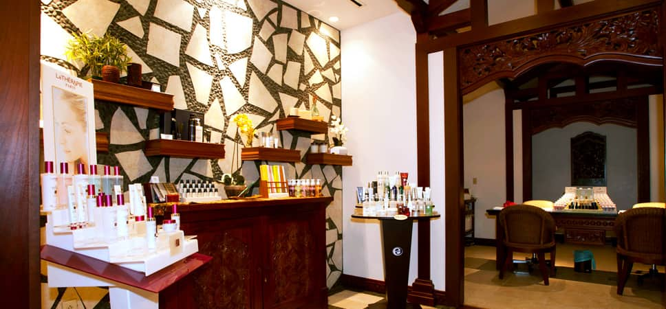 Wide shot of entry room of Mandara Spa with shelves of oils, lotions, polish and products.
