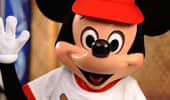 Mickey raises his white-gloved hand to give a high five.
