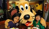 2 young Guests get a hug from Pluto.