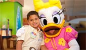 A brightly dressed Daisy Duck hugs a young Guest.