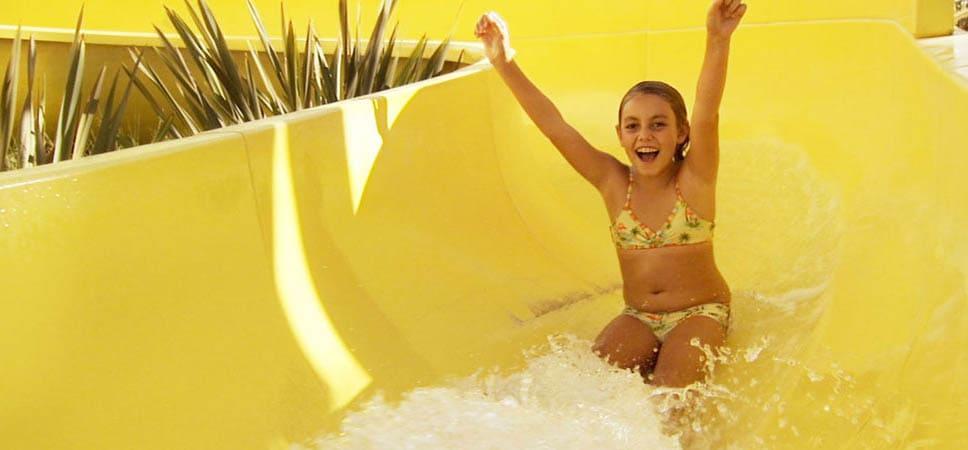 Una niña disfruta deslizándose en el tobogán de agua en el Disney's Paradise Pier Hotel