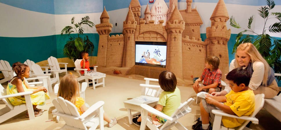 Kids sit in a circle of chairs around the sandcastle themed TV at the Paradise Theater.