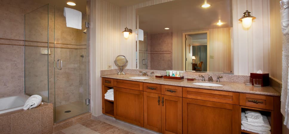 2 vanities, a large mirror, a shower stall, a bath tub and plenty of cabinet space.