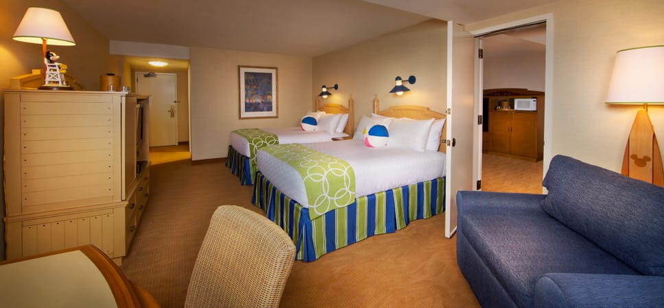 In the room: 2 queen-size beds, a large sleeping sofa, a large cabinet with dresser drawers and space for television.