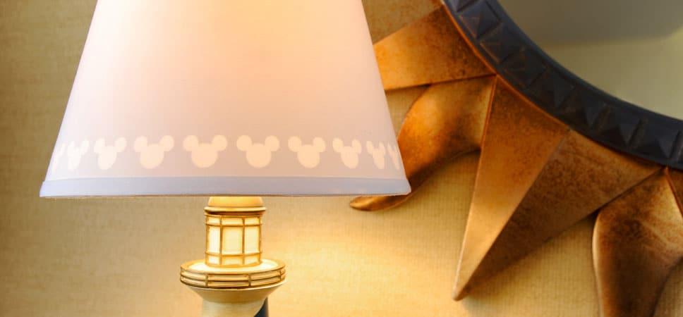 Detalles de una lámpara de mesa: en la pantalla, la silueta de Mickey, y en la base, un faro en miniatura.