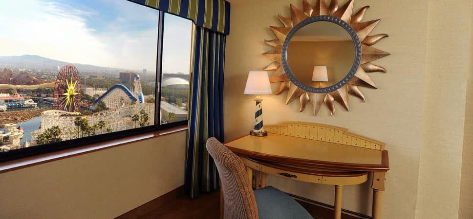 A yellow computer table beneath a mirror in a sun-shaped frame sit near a large window with a Theme Park view.