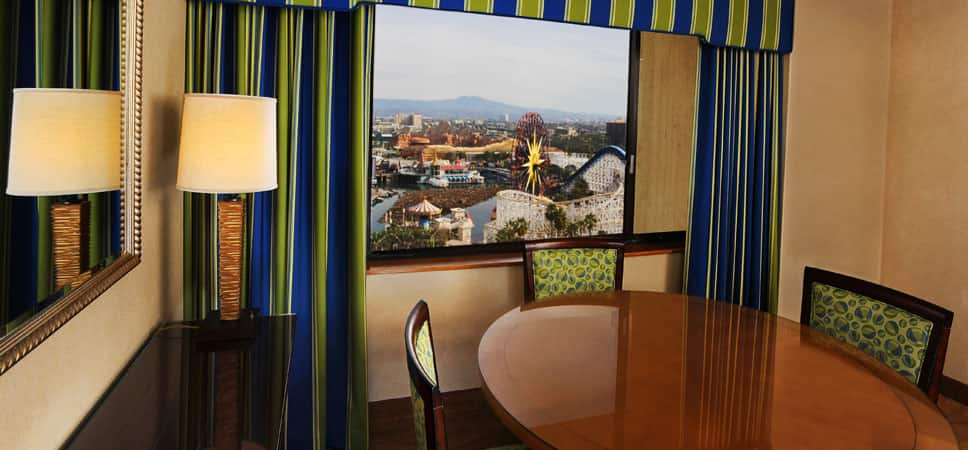 Dining table and chairs are positioned near a window with a Theme Park view.