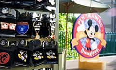 A pin-shaped circular sign outside a shop features Mickey Mouse and reads: Pin Trading Disneyland.