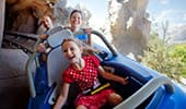 Excited Guests brace tightly while turning a corner on the Matterhorn Bobsleds at Disneyland Park