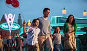 A family of 4 smiles excitedly while walking through Cars Land at Disney California Adventure Park