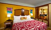 A king bed with 2 night stands near a shuttered privacy partition
