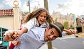 A smiling child on the back of a man in Cars Land at Disney California Adventure Park
