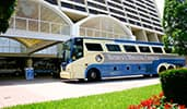 A Disney's Magical Express bus parked stopped at a hotel driveway