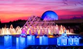 A chef stands behind an outdoor buffet station set up in front of a giant fountain at Epcot