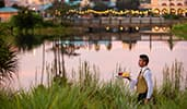 A Cast member carrying a tray of drinks outdoors by the water