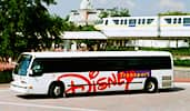 A Disney Transport shuttle is parked near a monorail track