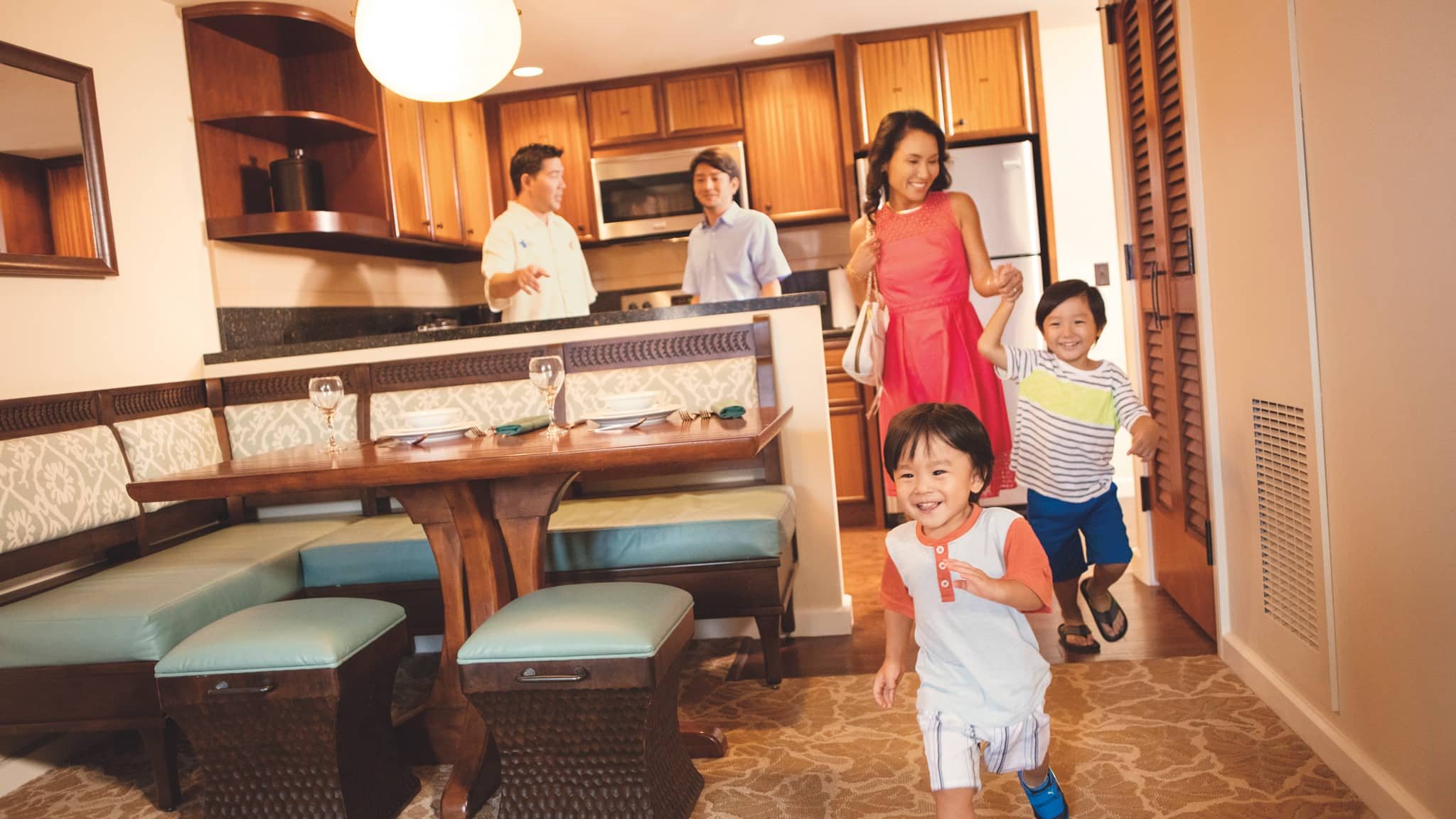 A mother, father and 3 children in the kitchen and dining area at Aulani