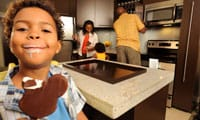Boy with ice-cream moustache eats a Micky-Mouse-Shaped ice cream bar in the kitchen of Bay Lake Tower at Disney's Contemporary Resort