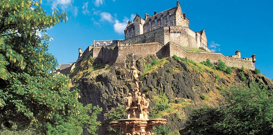Edinburgh Castle with golden statue fountain in foreground