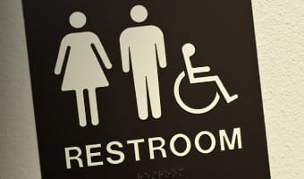 A restroom sign with icons of a woman, a man and a wheelchair