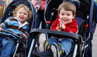 Two toddlers enjoy a ride in side-by-side strollers