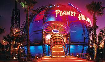 The flying saucer-like entrance to Planet Hollywood lit up at night