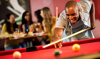 A cheerful young man plays pool at Splitsville Luxury Lanes in Disney Springs