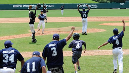 Several baseball players on a field, raising their arms in celebration