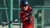 A teenage baseball player swings his bat
