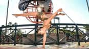 A girl in a leotard performs a one handed handstand